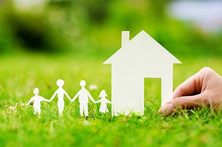 hand holding paper cutouts of house and family