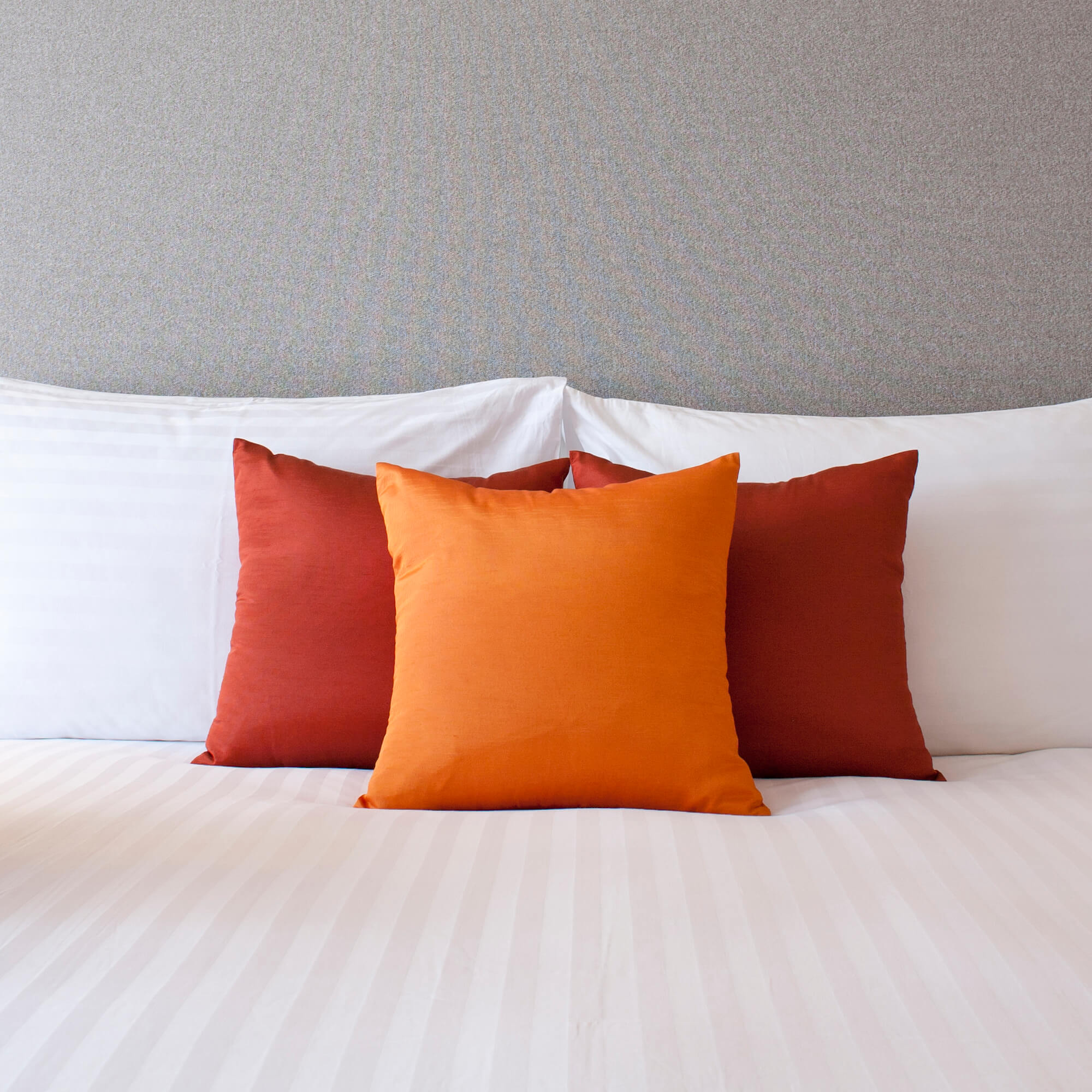 A hotel bed with three colorful pillows