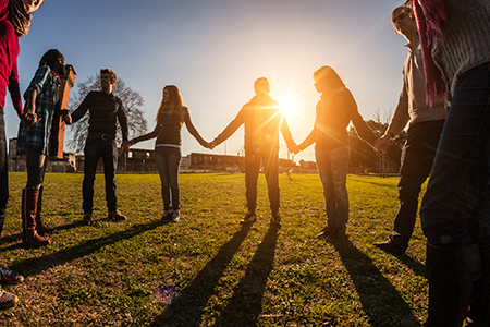 group of people holding hands with sun setting behind them
