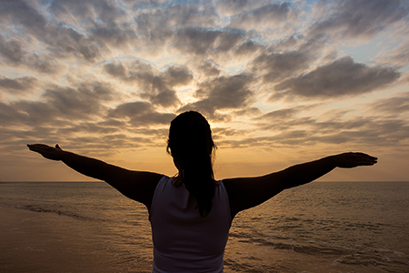 woman lifting arms in joy with sunset background