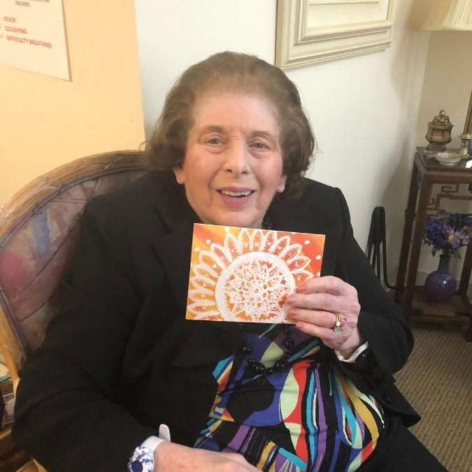 senior adult holding greeting card made by volunteers