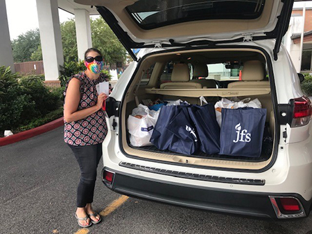 volunteer loading car with Rosh Hashanah meals to be delivered to seniors