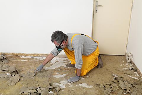worker repairing floor of flooded home