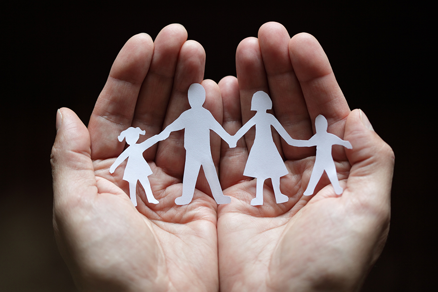 open hands holding paper figures of family