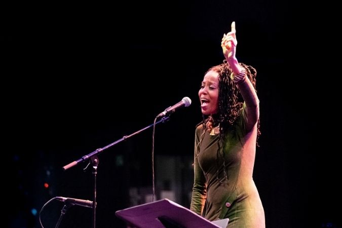 Toni Hickman points to the sky while performing at ReelMusic