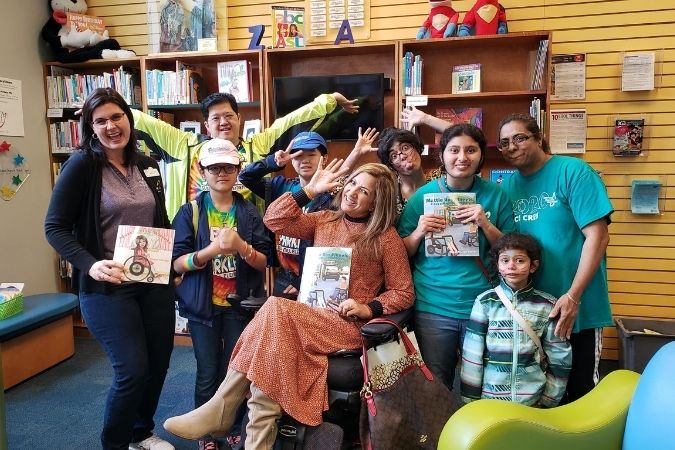 Meena Outlaw and several children pose for a photo with Meena's book