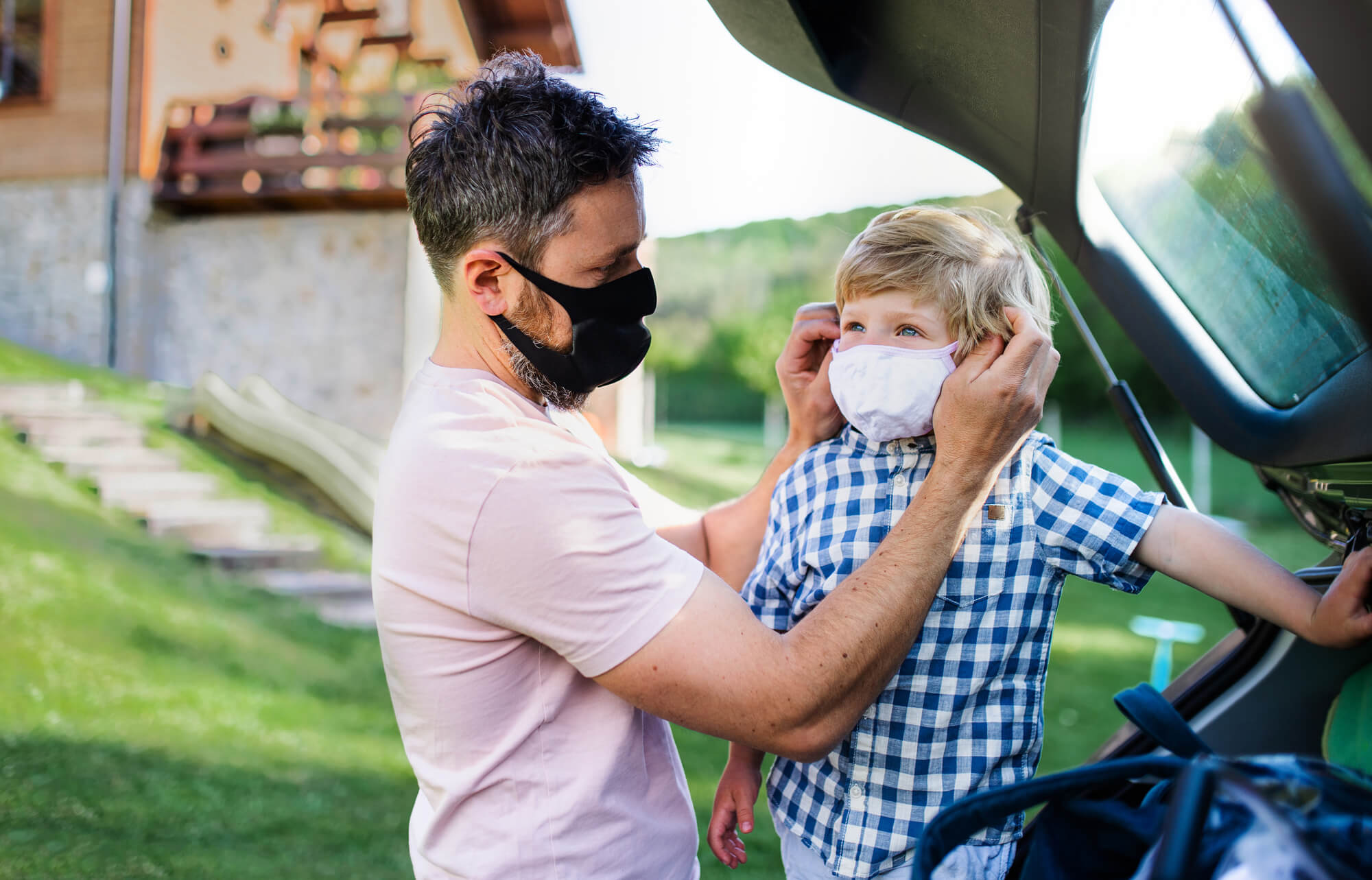 Man putting mask on young son