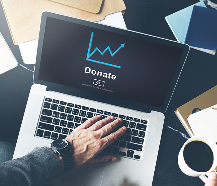 open laptop with graph going up and the word donate