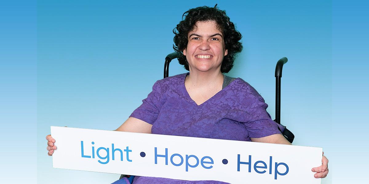Gabby holding Light Hope Help sign