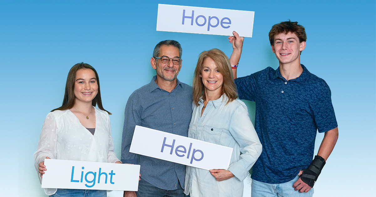 Lewis family holding Light Hope Help signs