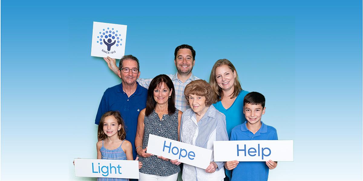 Wishnow family holding Light Hope Help signs