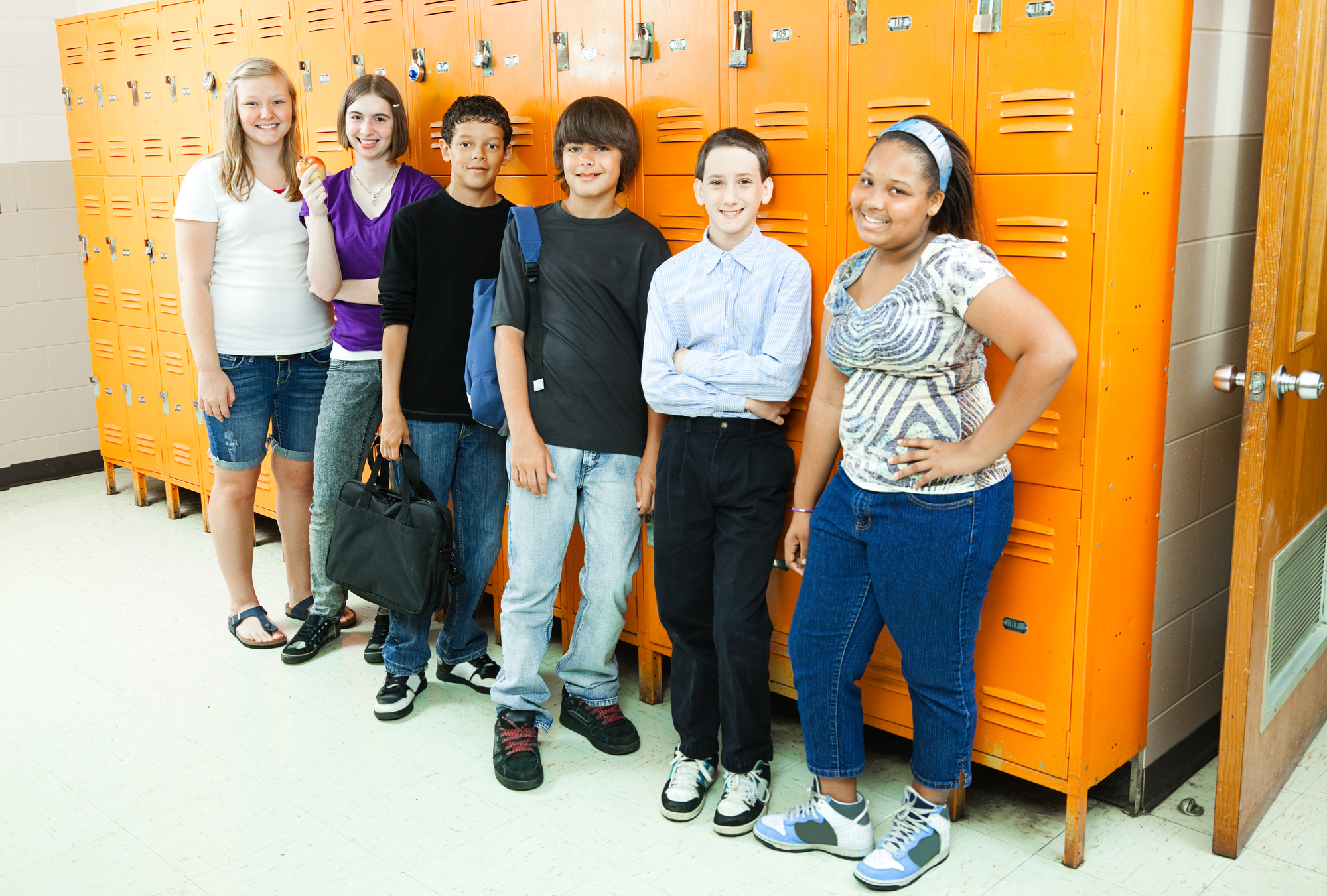 Group of teens standing in front of a row of lockers