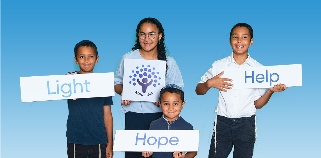 group of four children holding Light Hope Help signs