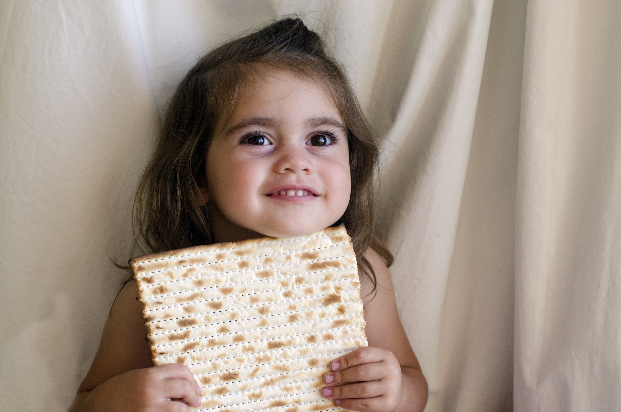 Young girl holding piece of matzos