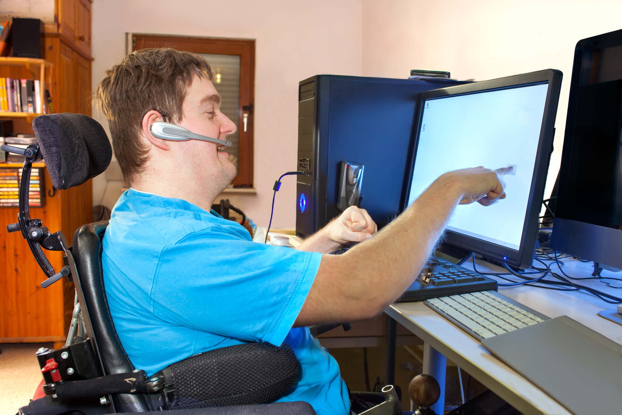 Man in wheelchair with headset participating in virtual meeting