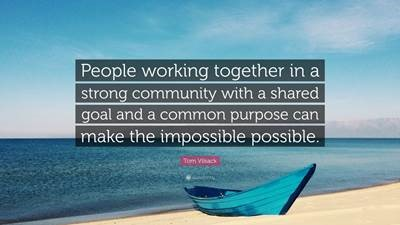 People working together in a strong community with a shared goal and a common purpose can make the impossible possible. Boat on sand with ocean behind.