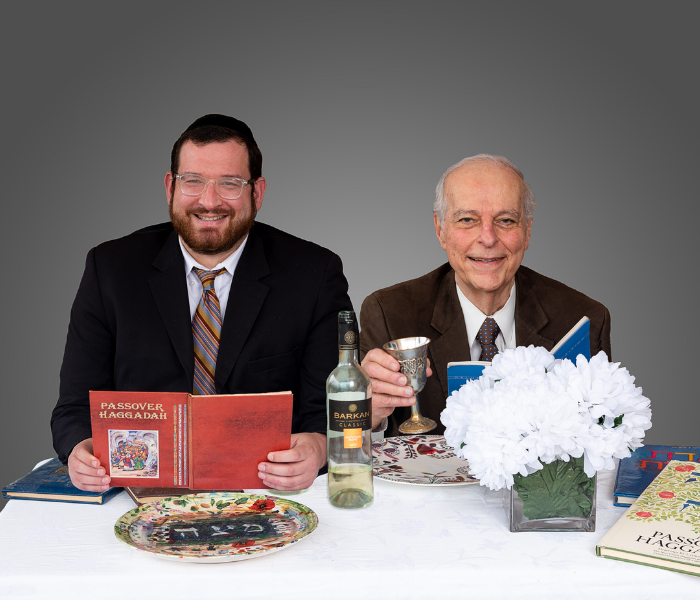 Rabbi Asher Block and Barry Goodfriend, M.D. sit a traditional seder table