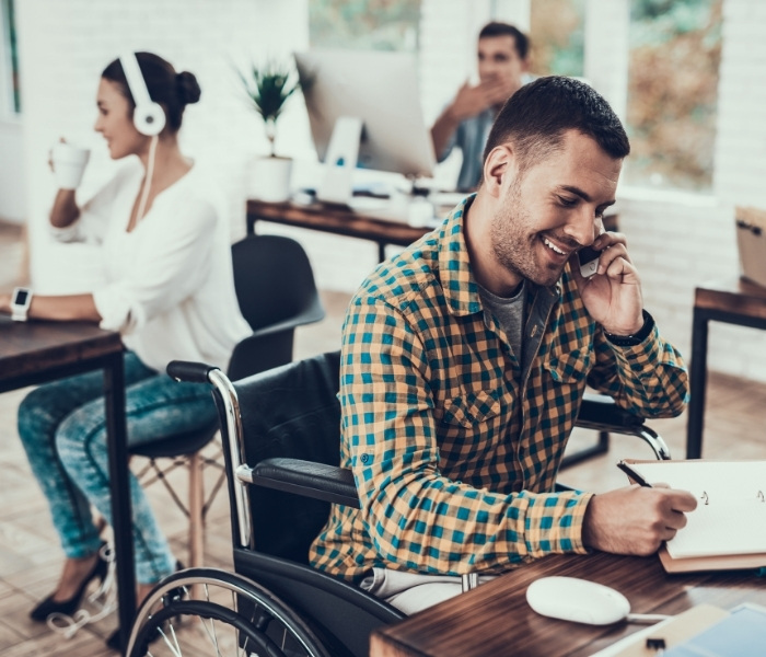 A man using a wheelchair works in an office with two collegues in the background