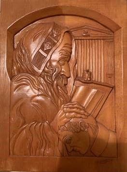 an intricate wood carving depicting a holy man holding a Torah and blessing a young boy