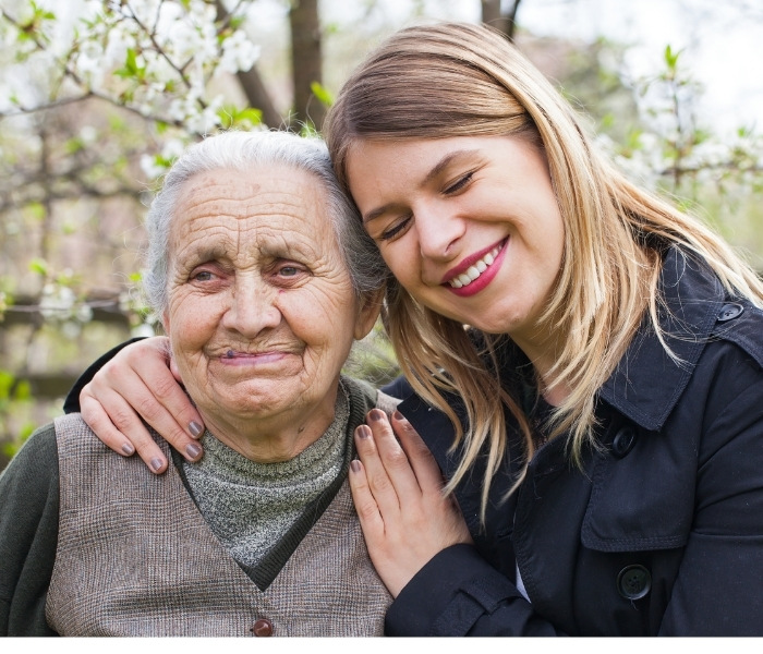 A young woman smiles while hugging an older woman