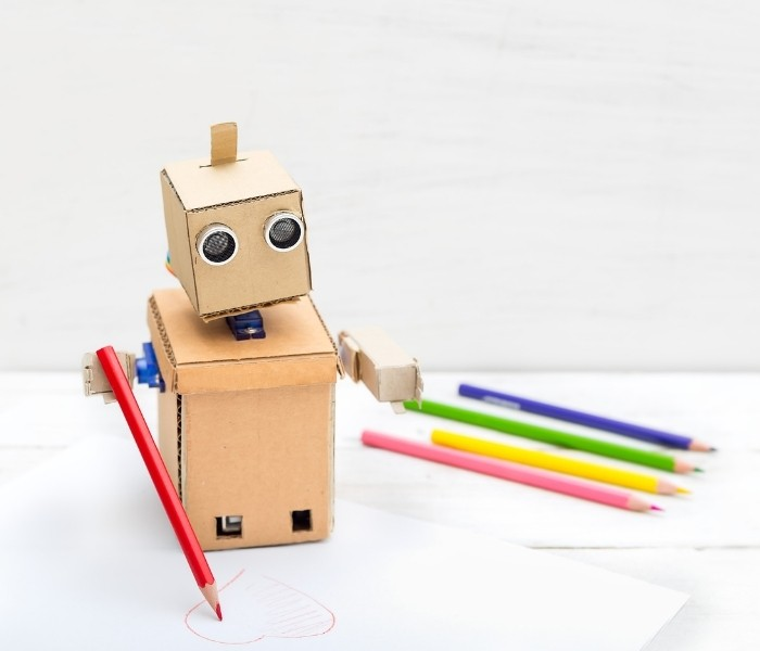 A cardboard robot with colored pencils in the foreground