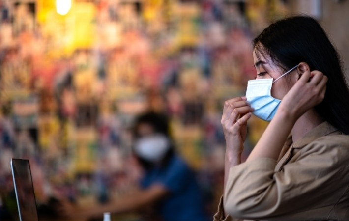 a young woman sits at a cafe and prepares to take off her mask
