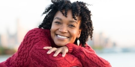 Woman wearing red sweater smiling outdoors