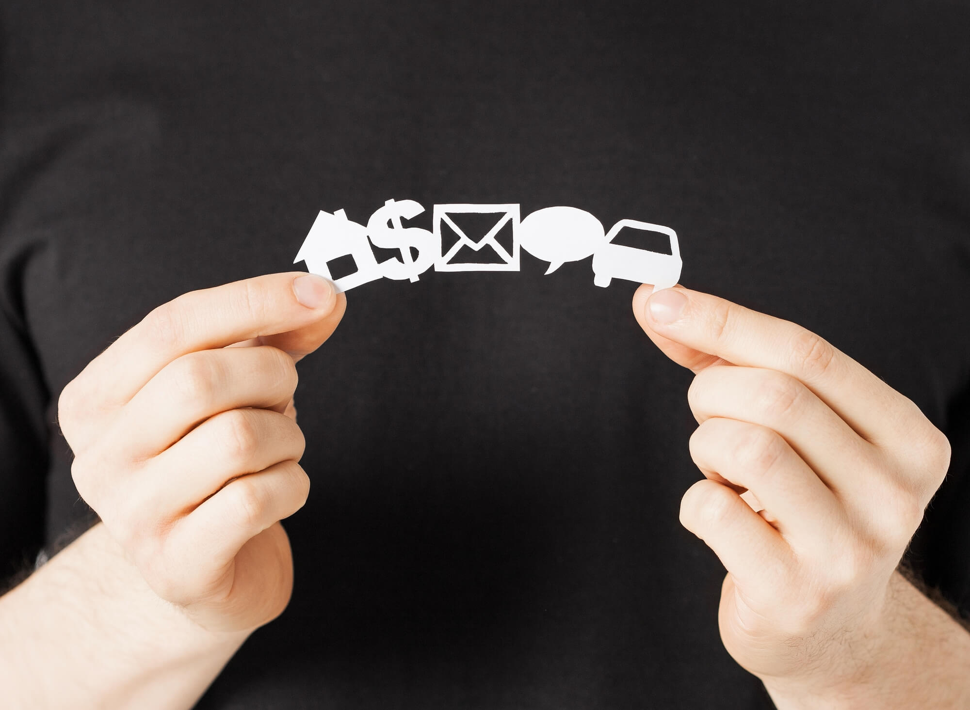 Two hands holding a paper cut out of a house, dollar sign, envelope, message bubble and car
