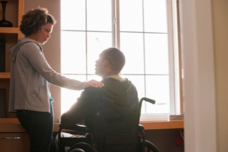 a woman puts her hand on the shoulder of a man in a wheelchair