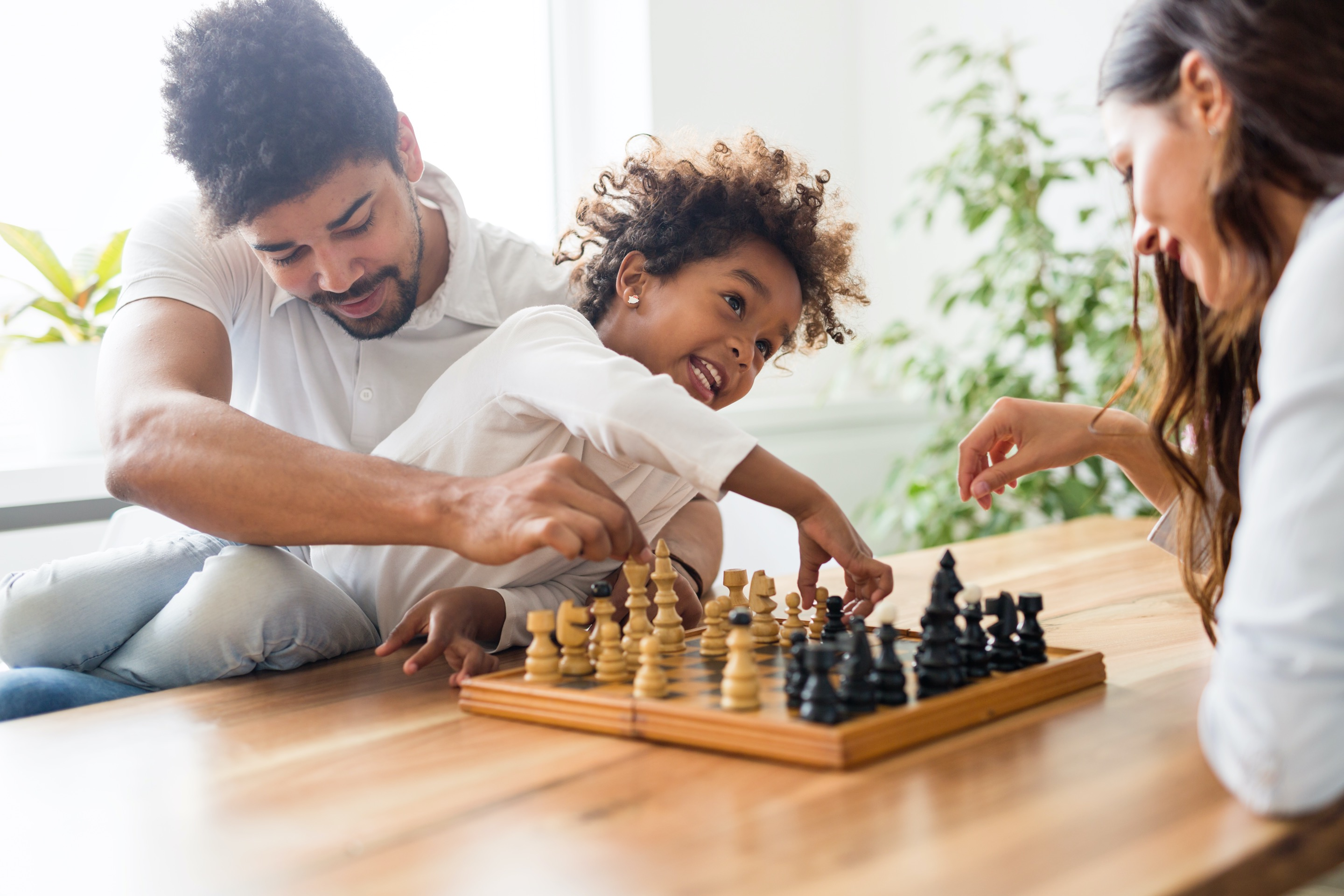 Photo of a family playing chess together
