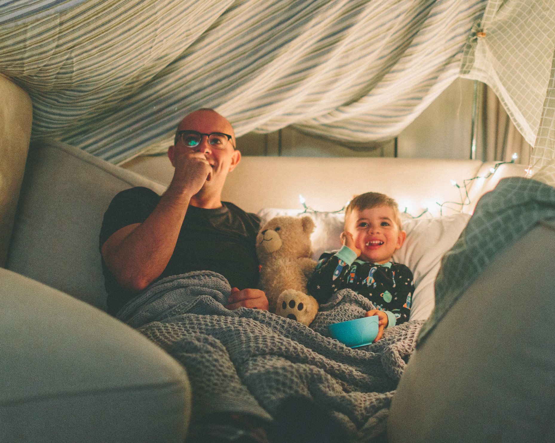 A little boy and his dad watching TV from their pillow fort