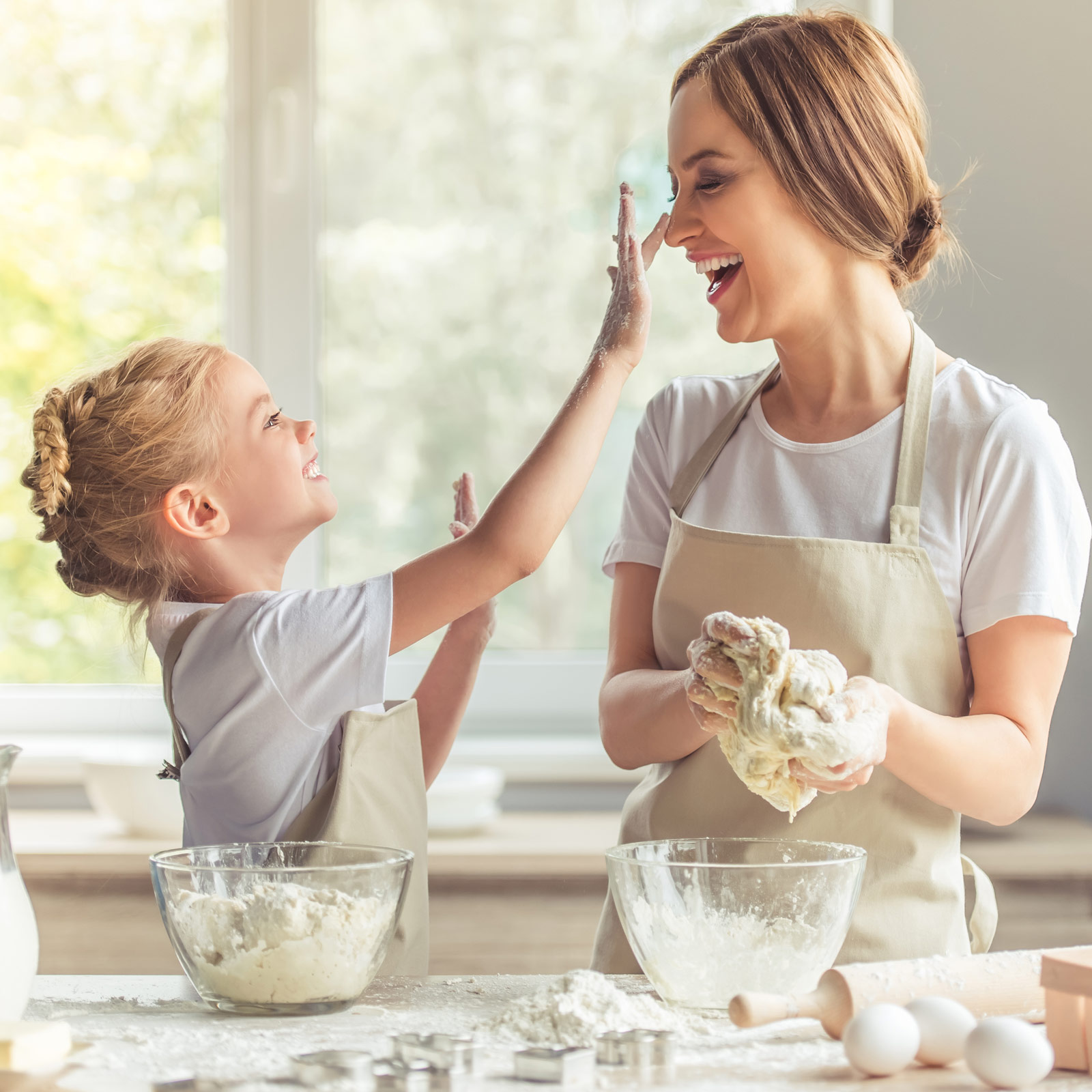 A mother and daughter baking cookies and playing with the ingredients