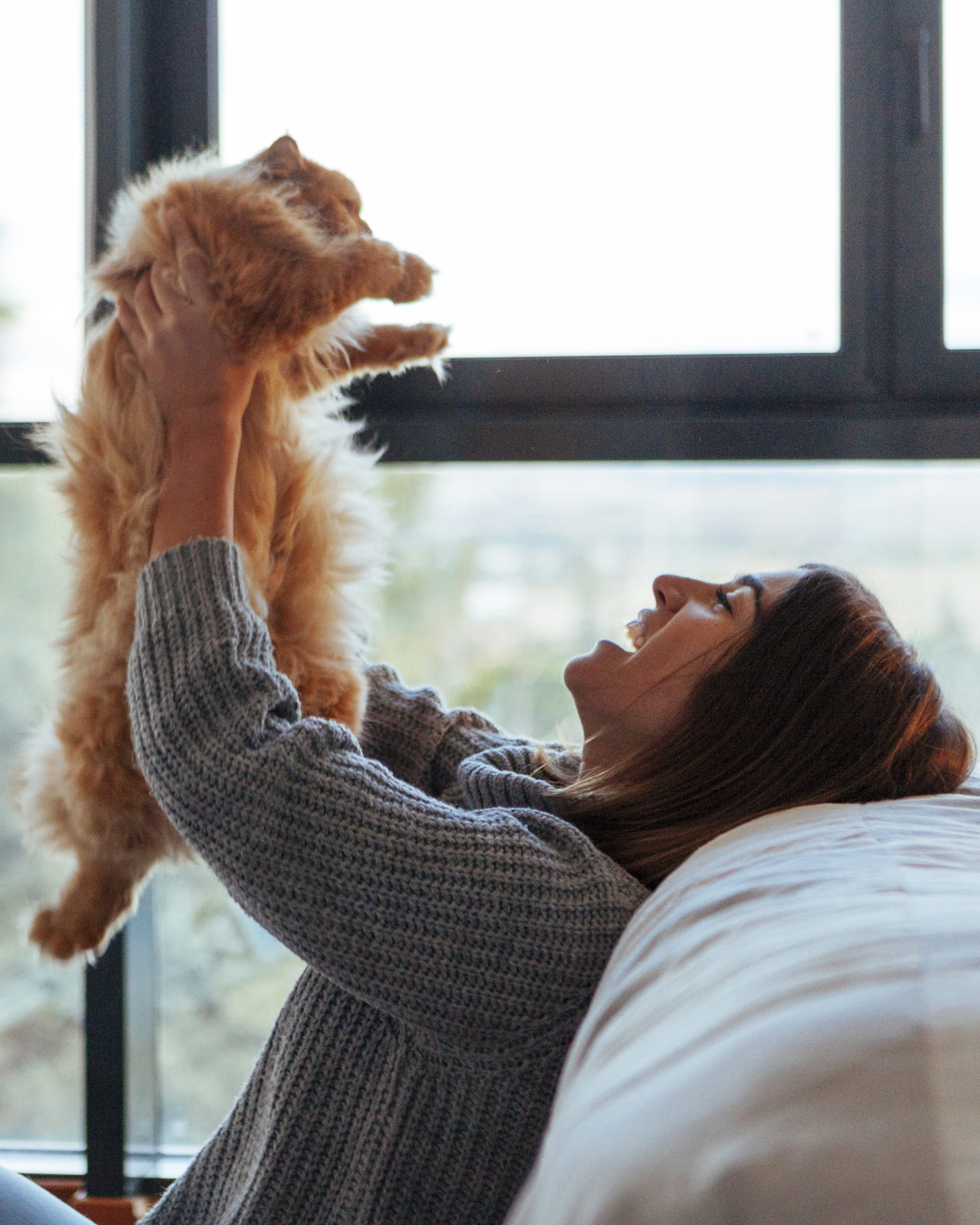 Woman lifting her cat into the air