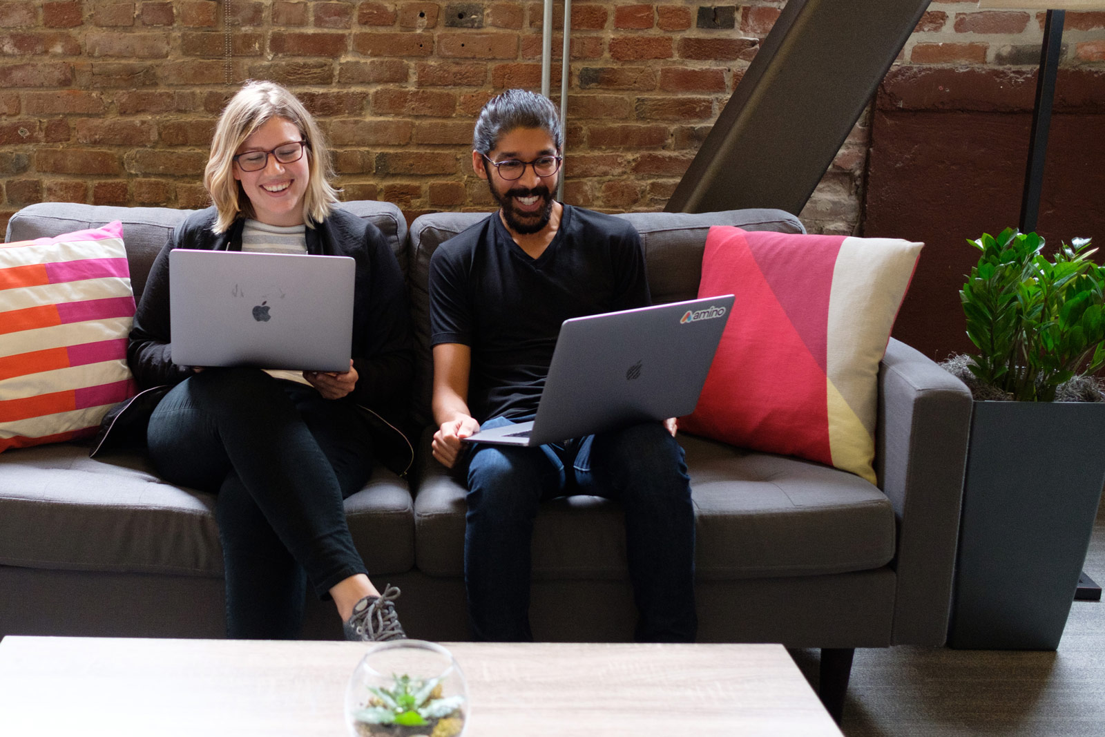 Amino teammates collaborating with laptops on a couch