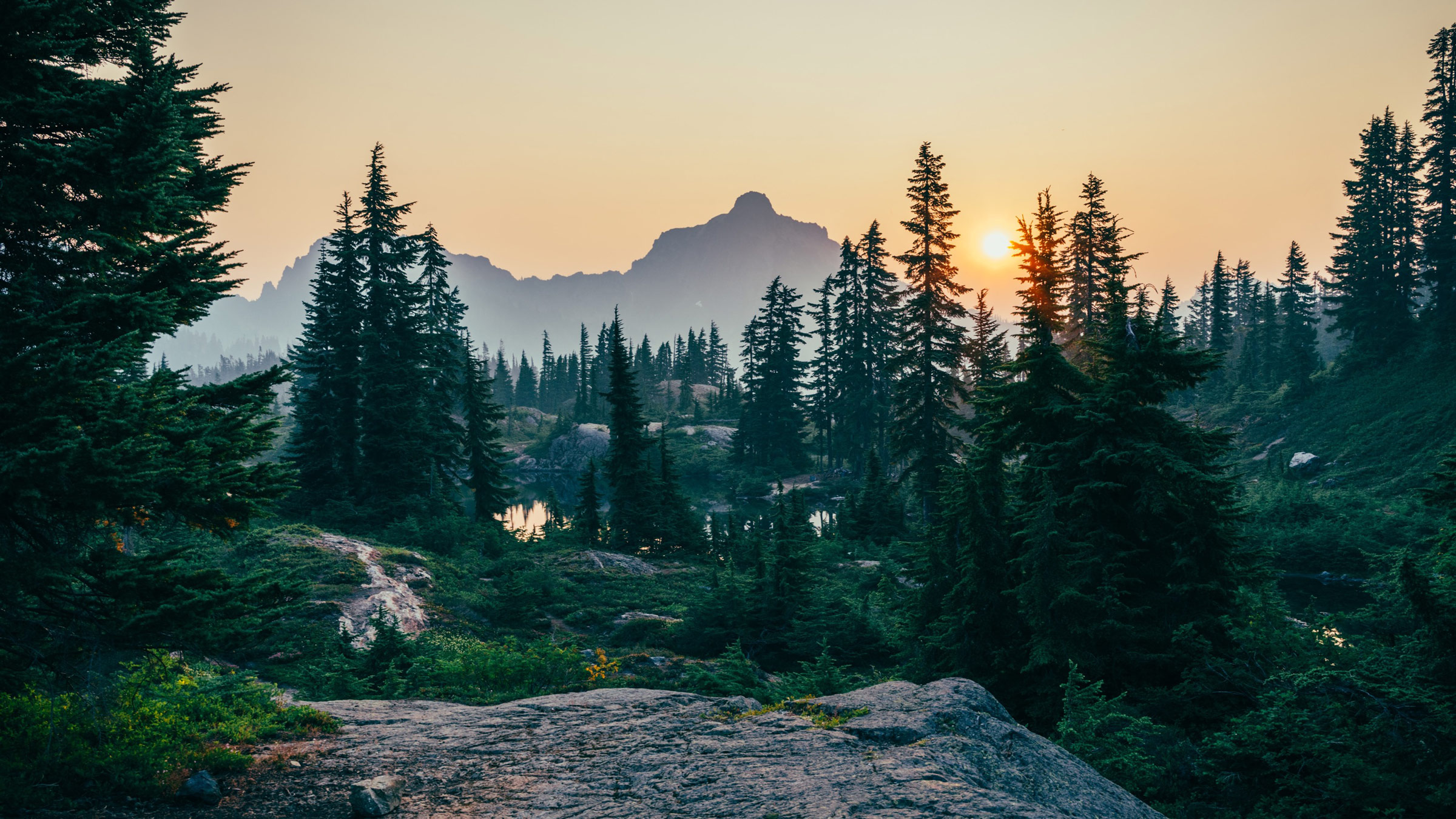 Photo of a sunrise through the mountains and trees