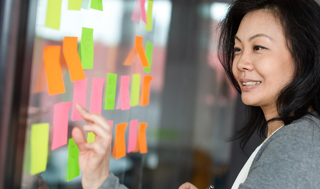 Photo of a woman brainstorming employee benefit plan ideas using post-it notes