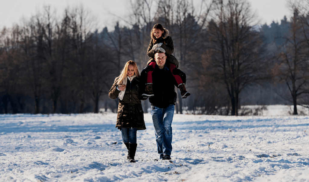 Happy family walking together in the snow