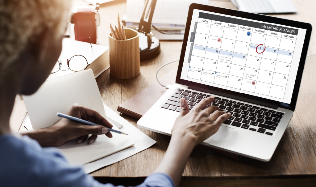 Photo of a HR manager reviewing a calendar on a laptop