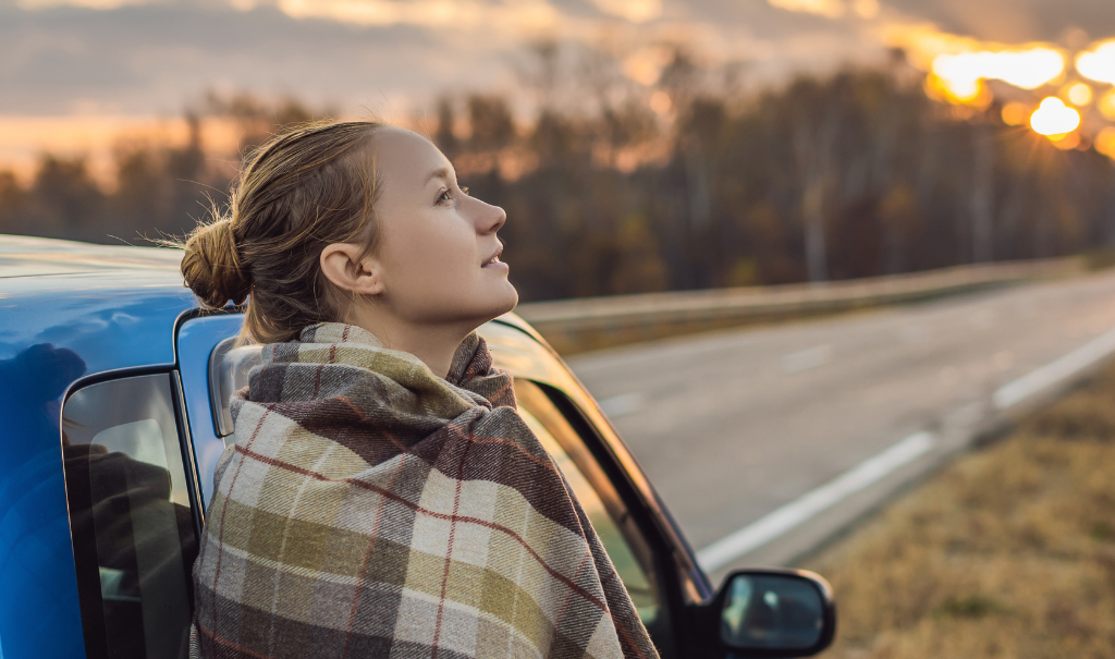 Woman standing next to her car looking at the road ahead