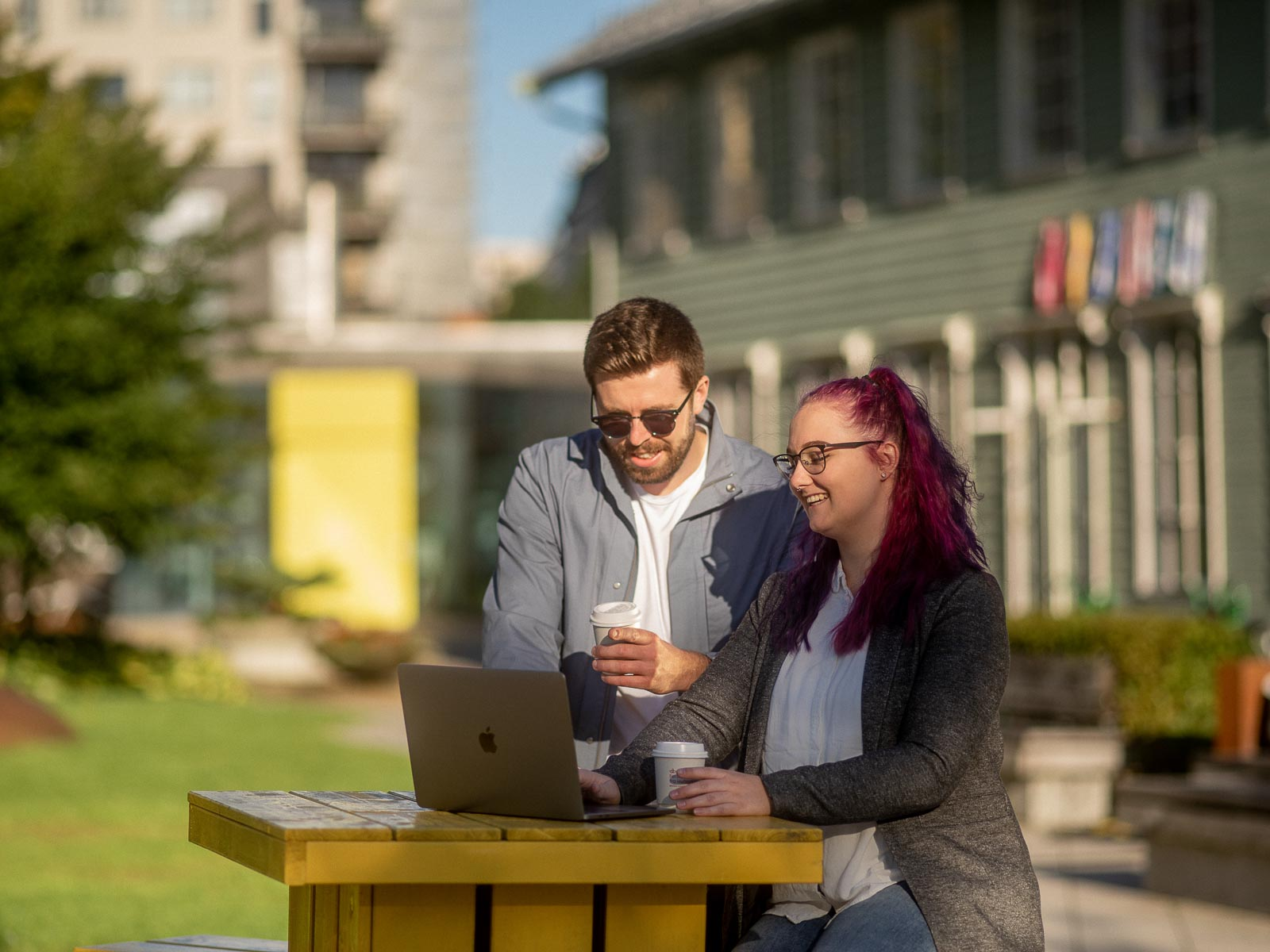 Mann og kvinne jobber på laptop utendørs