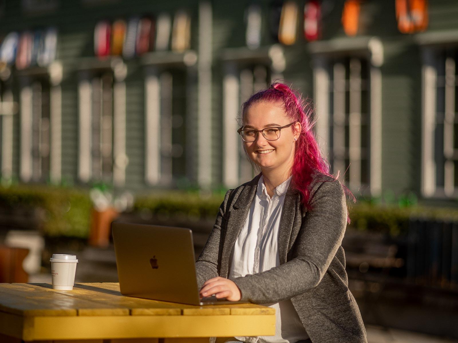 Kvinne nyter finværet ute og jobber på laptopen