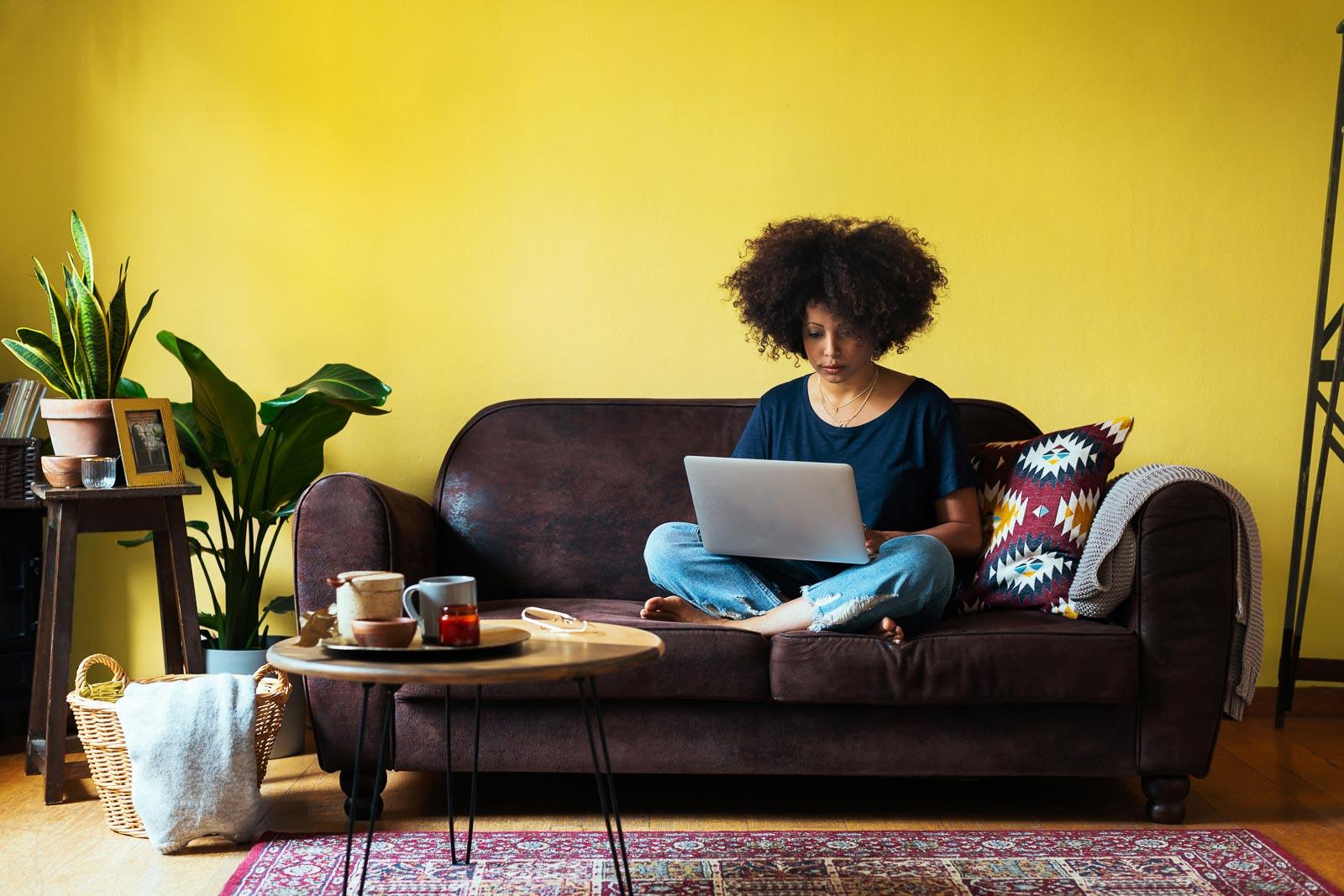 Kvinne sitter i sofaen og jobber med SSL-sikret nettside