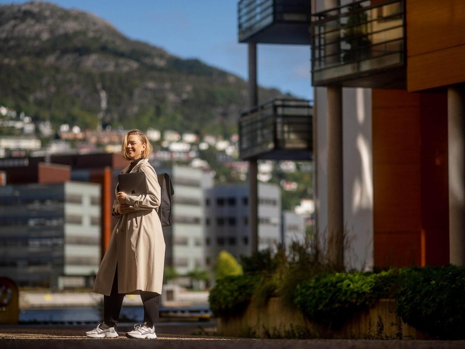 Kvinne nyter solen på damsgård med laptop i hånden
