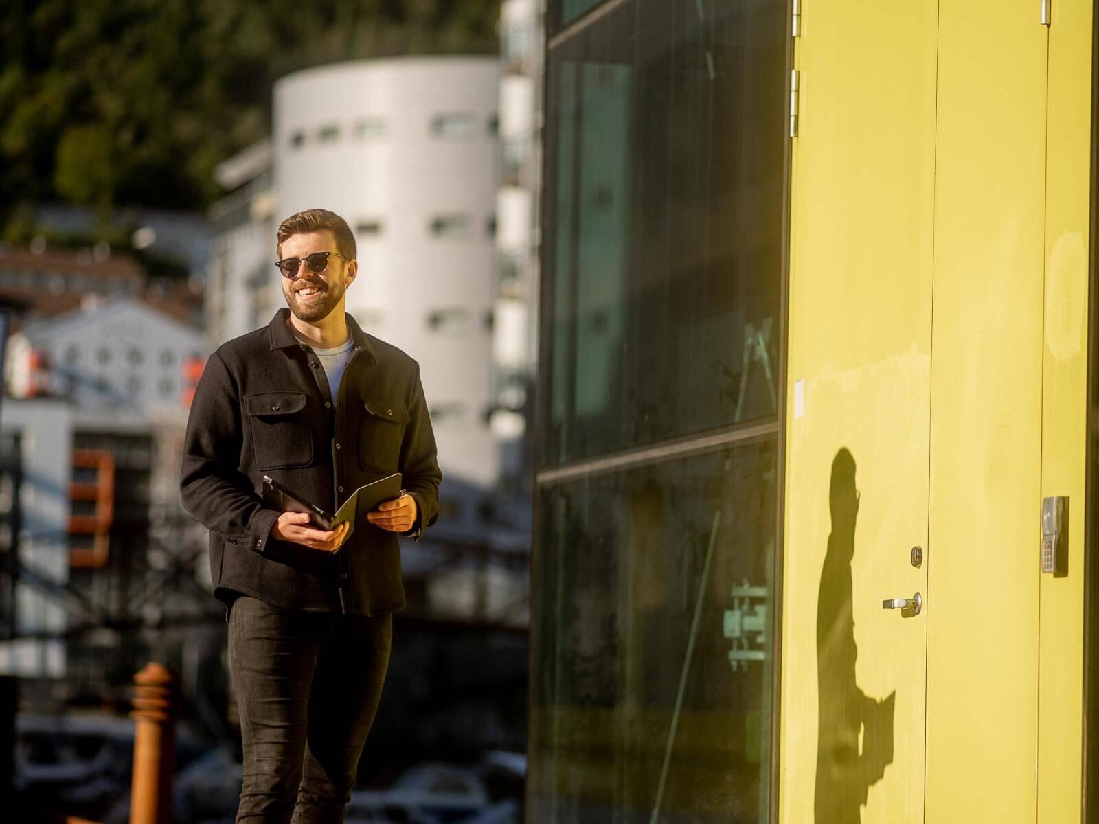 Mann står utendørs i solen med ipad i hånden