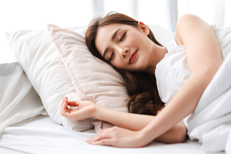 young woman comfortably sleeping on her bed