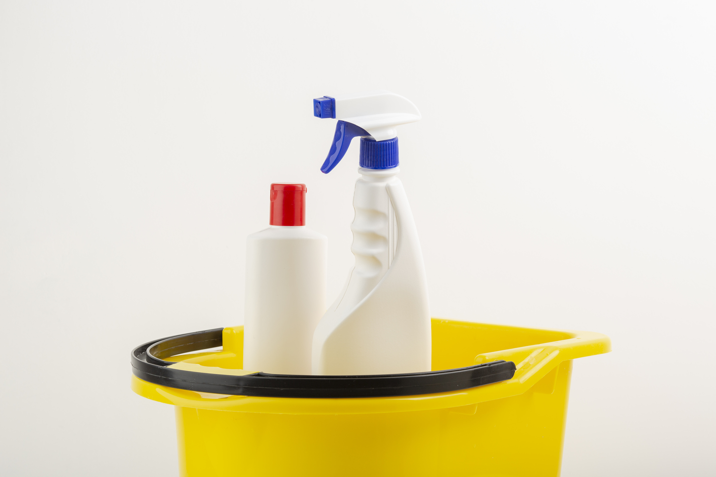 cleaning bottle sprays in yellow bucket