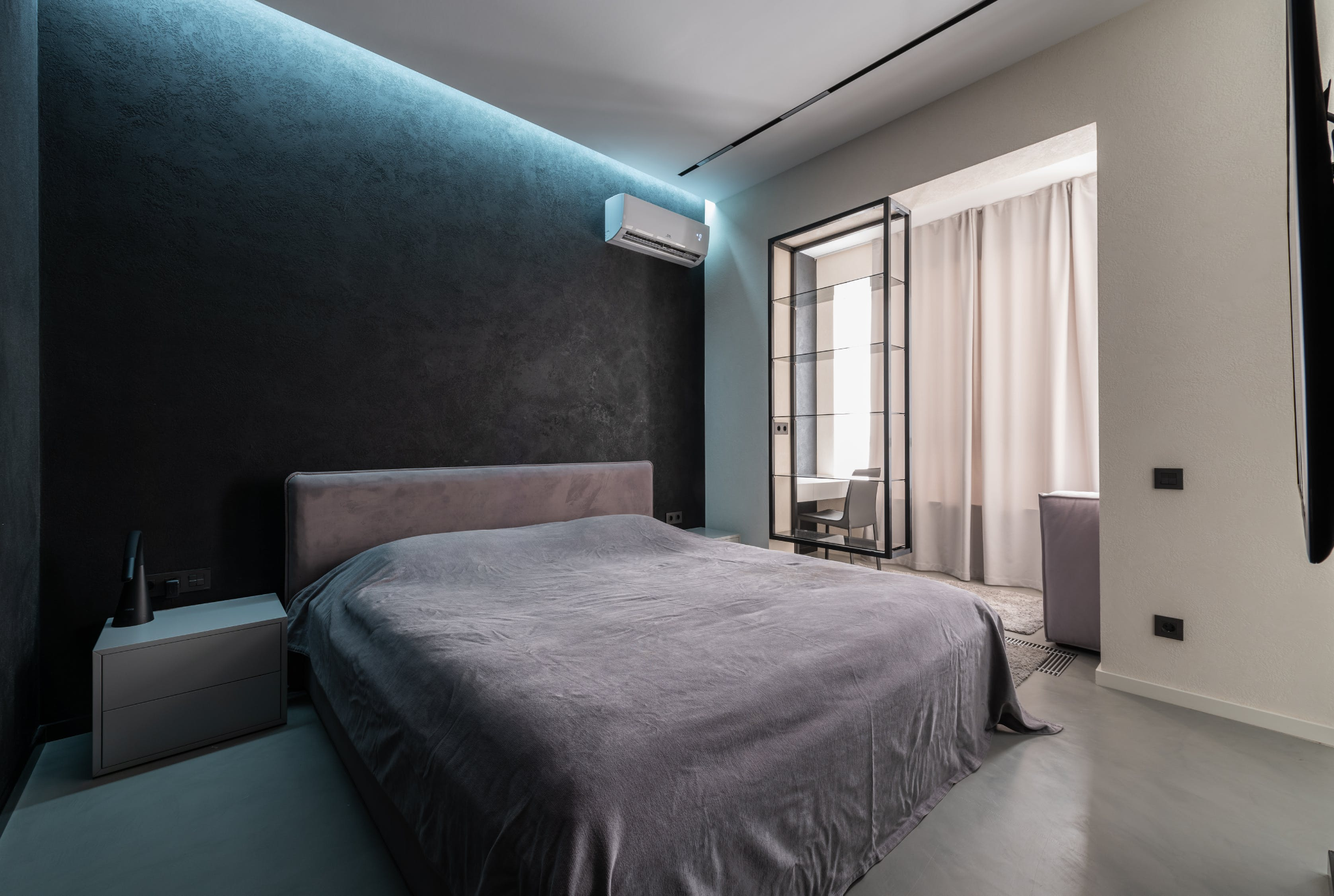 Modern bedroom with black walls, grey bed, and split-type air conditioner