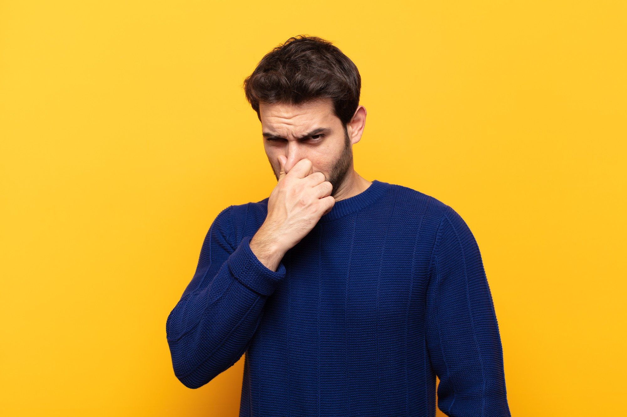 Man holding nose and grimacing
