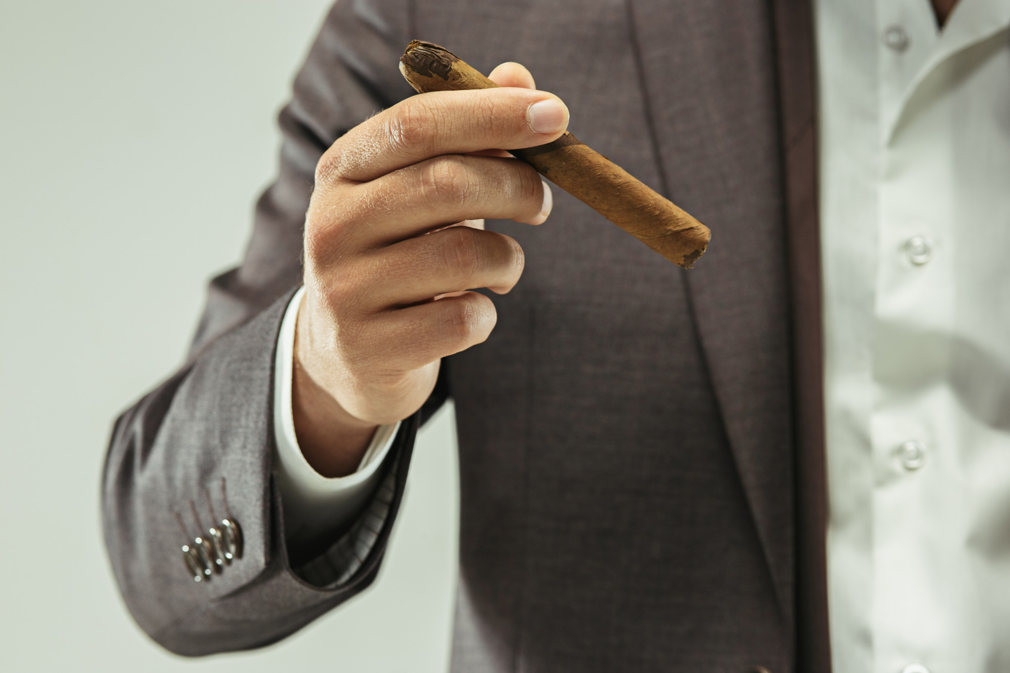 man in suit holding a cigar
