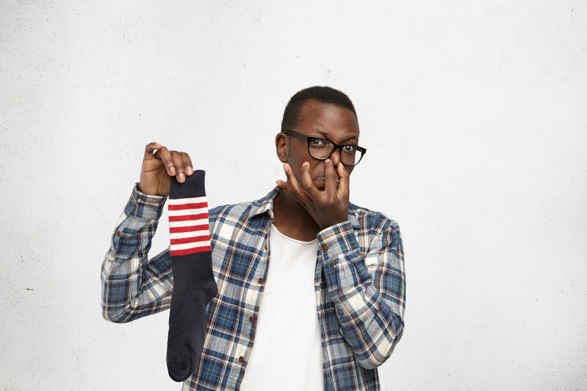 man with glasses holding up sock in one hand, holding nose in other hand